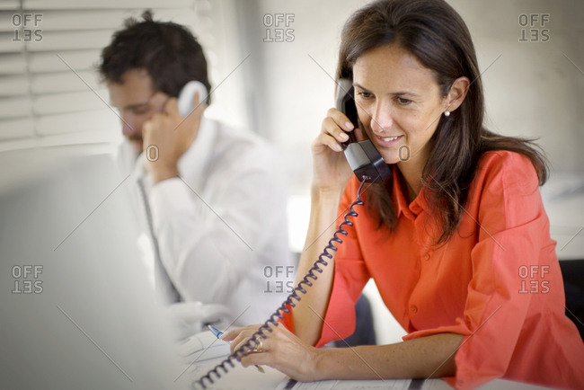 Smiling mid-adult businesswoman talking on a telephone inside an office.
