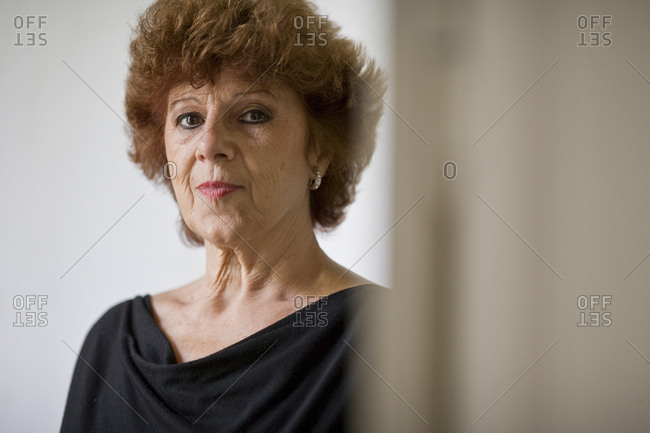 Portrait of a mature woman standing in a room.