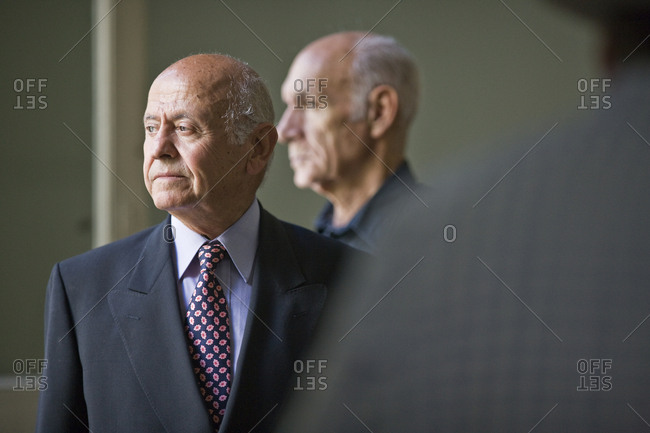 Senior adult man standing in a room with a friend behind him.