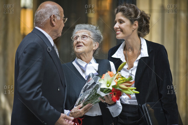 Senior woman holding flowers with her husband and mid-adult daughter while talking in a foyer.