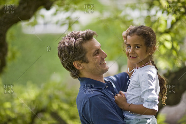 Portrait of a smiling young girl being held by her father while outside in the garden.