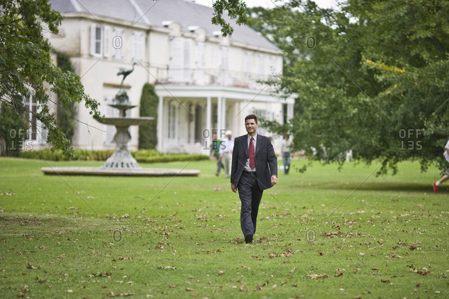 Businessman walking across a lawn