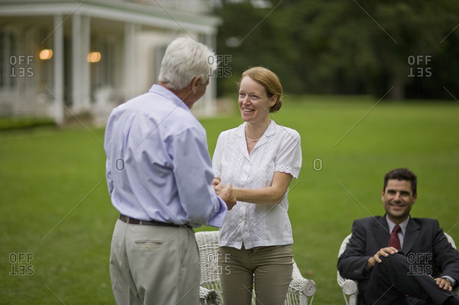 Mid-adult woman  talking with her senior father while her husband sits and watches.