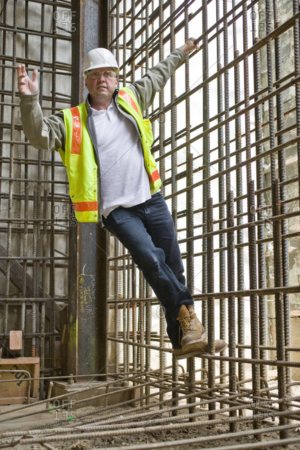 Portrait of a male construction worker hanging from a wire grid on a construction site.