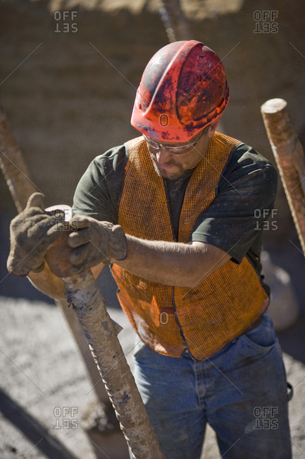 Dirty mid-adult construction worker wearing a helmet and safety glasses while working on a construction site.