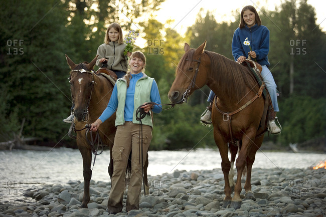 Portrait of a mid-adult woman walking beside her two teenage daughters on horses.