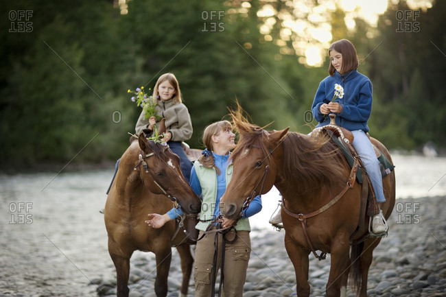 Mid-adult woman walking beside her two teenage daughters on horses.