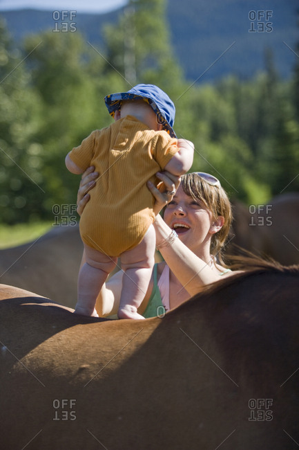 Mother standing baby up on the back of a horse