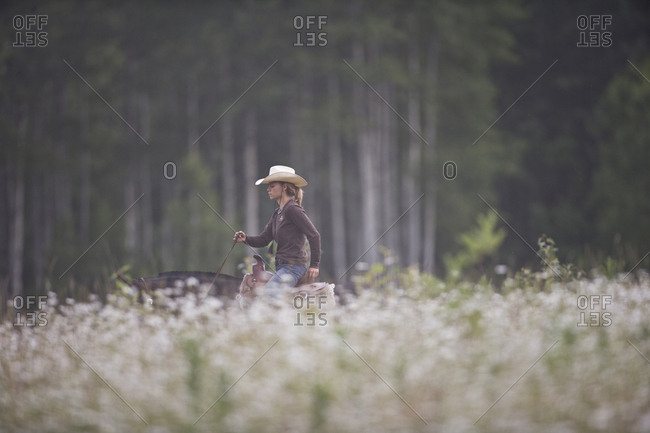Young woman riding horse through meadow