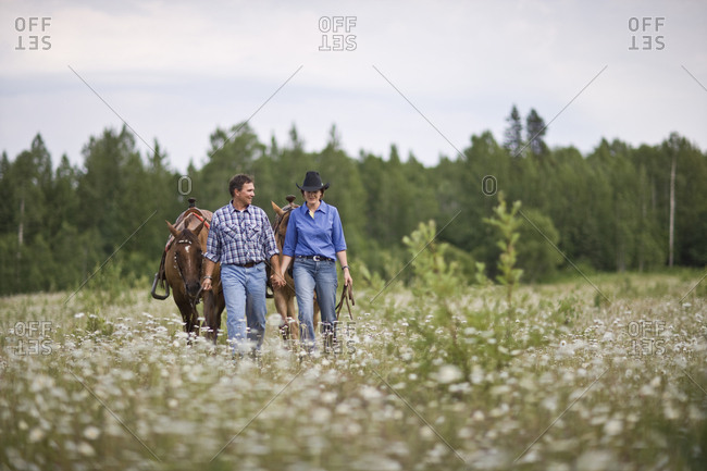 Mature couple leading horses through a meadow