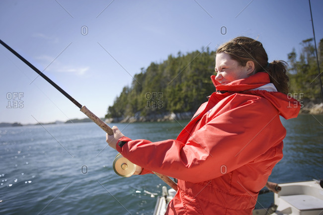 Teenage girl fishing on a boat.