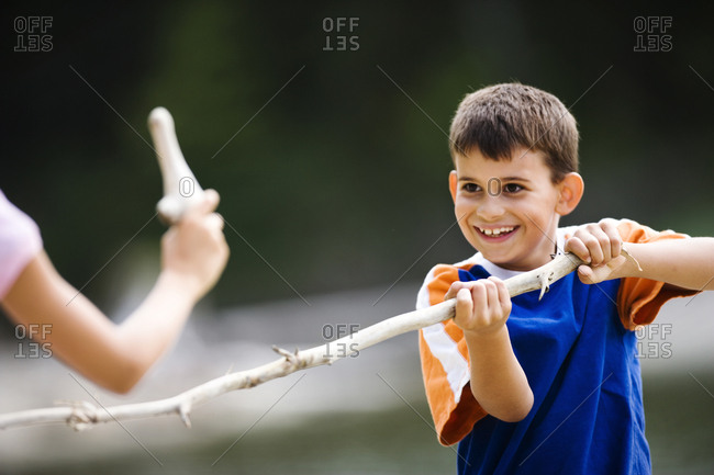 Smiling young boy holding a stick.