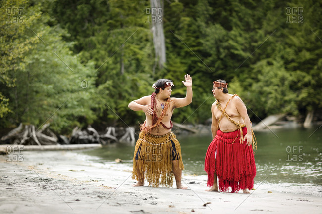 Two mid-adult men having fun wearing traditional skirts on a beach.