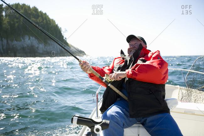 Mature adult man sitting on a boat fishing.