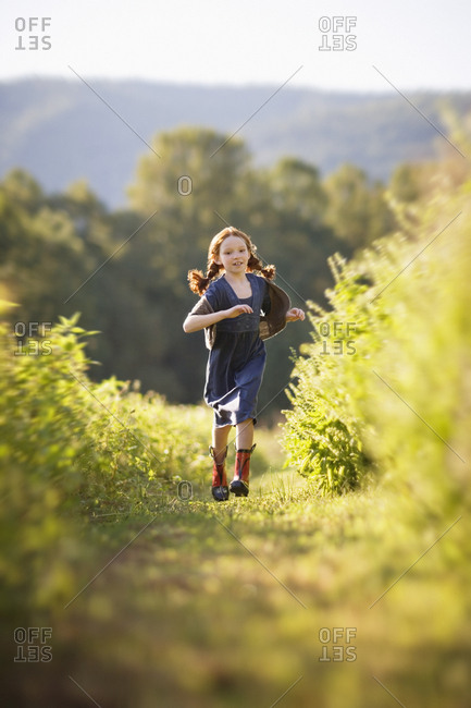 Young girl with her hair in braids running through an overgrown field in the country.