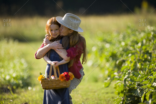 Portrait of a young girl being kissed by her mid-adult mother while on a farm.