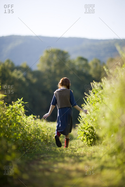 Young girl walking down through a field.
