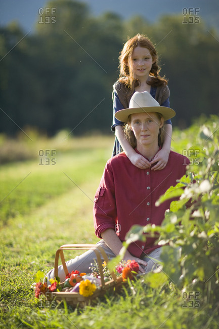 Portrait of a young girl with her arms around her mid-adult mother's neck while on a farm.