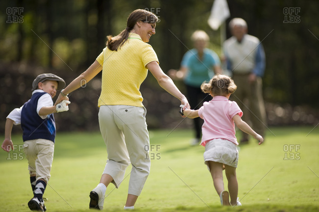 Mother holding hands and skipping with children on golf course