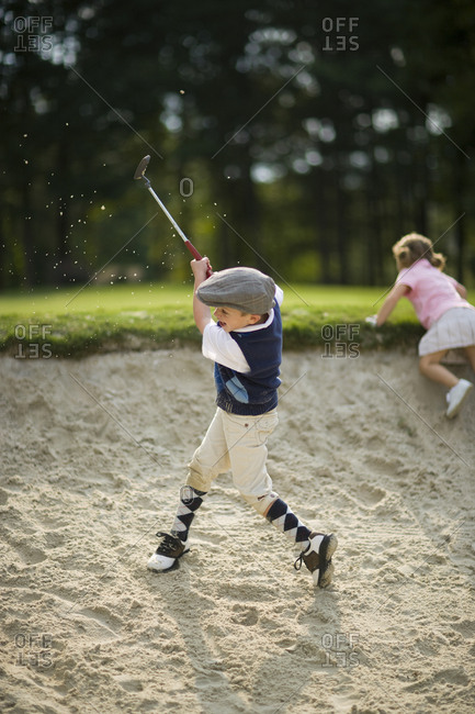 Young boy playing with a putter in a sandpit on a golf course.