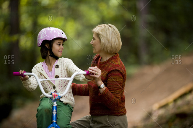 Grandmother helping her granddaughter ride a bike