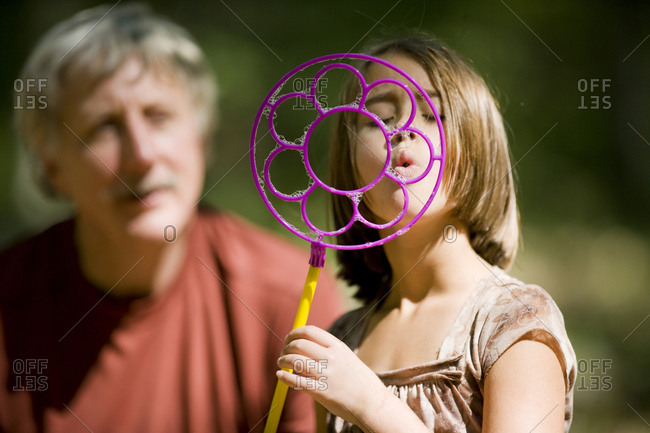 Grandfather and granddaughter blowing bubbles
