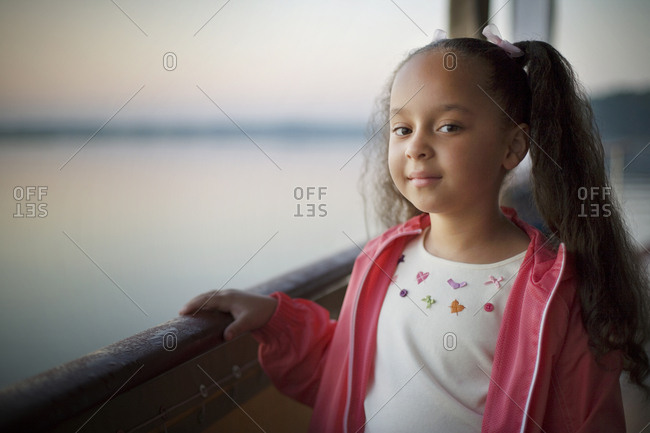 Portrait of a young girl standing on a boat at sea.