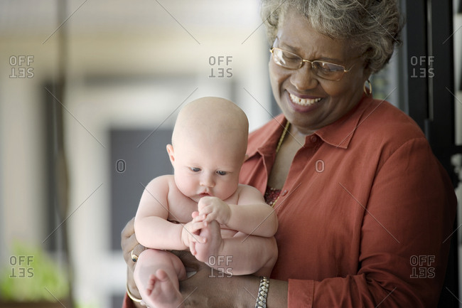 Baby being held by a mature adult woman.