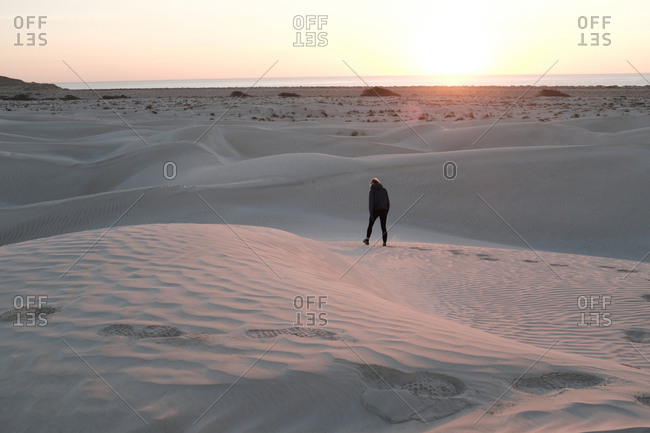 Person walking and leaving footprints through coastal sand dunes at sunset