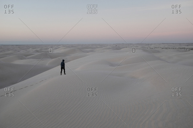 Person trekking across sand dunes