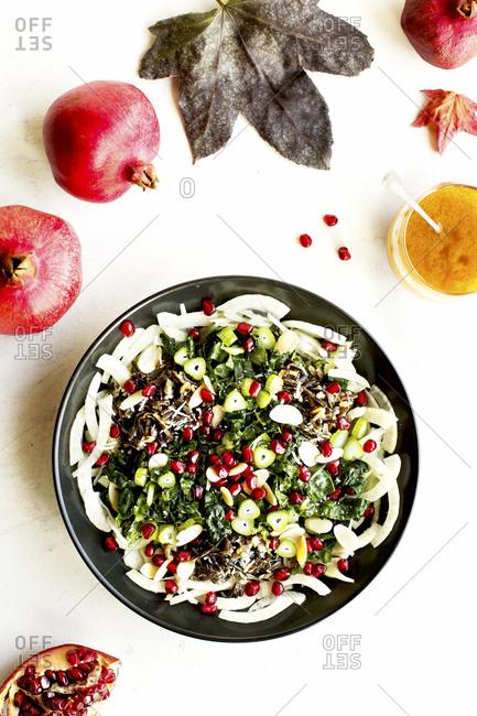 Homemade kale salad with whole pomegranates and vinaigrette salad dressing