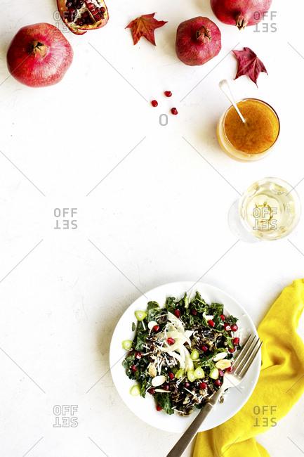Plate of kale salad with whole pomegranates and vinaigrette salad dressing