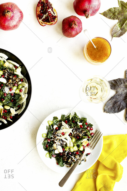 Homemade kale pomegranate salad served with vinaigrette salad dressing and wine
