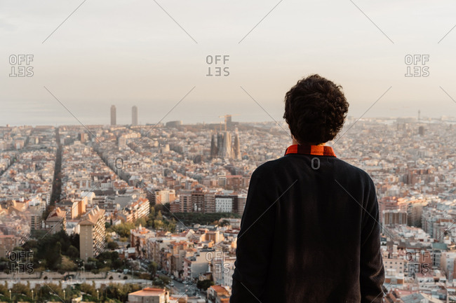 Back view of male in casual outfit admiring view of majestic metropolis and gray sky