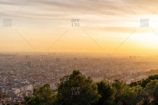 Beautiful view of amazing bright sun setting on cloudy sky over metropolitan city and hill