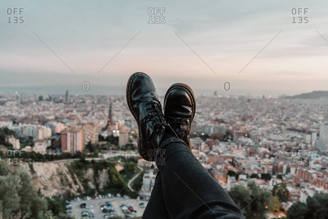 Feet of anonymous traveler against?beautiful metropolitan city and fantastic cloudy evening sky