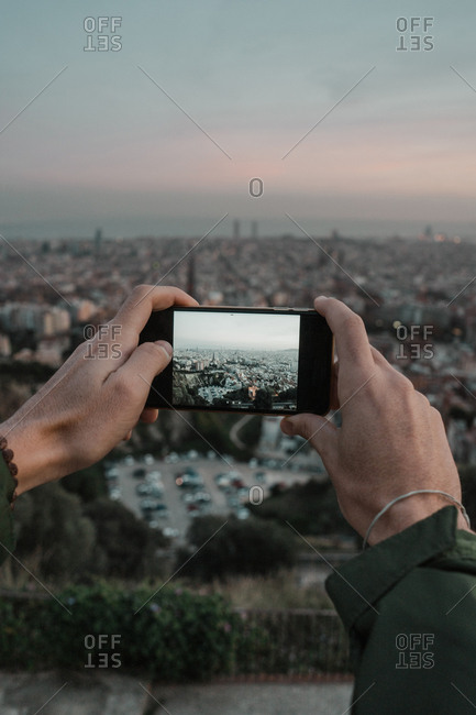 Man hands using modern smartphone to take pictures of amazing metropolitan city in wonderful cloudy evening