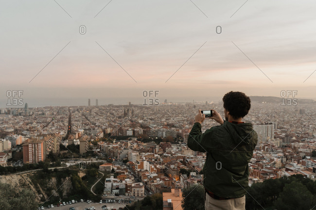 Back view of man in casual outfit using modern smartphone to take pictures of amazing metropolitan city in wonderful cloudy evening