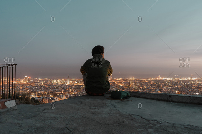 Back view of male traveler sitting on concrete floor and looking at brightly illuminated metropolis at beautiful night
