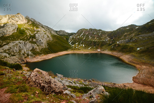 Breathtaking view of small lake with clean water located near beautiful green mountains on cloudy day in countryside in Asturias, Spain