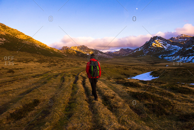Back view of person with backpack walking on dry grass of wonderful valley towards spectacular mountain ridge