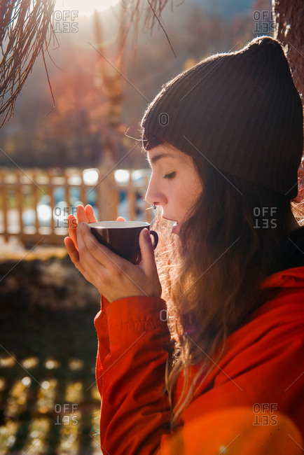 Side view of beautiful young female in stylish hat keeping eyes closed and smelling aromatic hot drink while sitting in countryside on sunny day