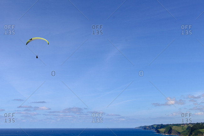 Magnificent drone view of bright paragliders flying against cloudy sky over beautiful green nature on sunny day