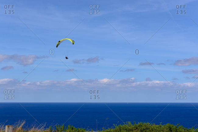 Magnificent drone view of bright paragliders flying against cloudy sky over beautiful green nature and sea on sunny day