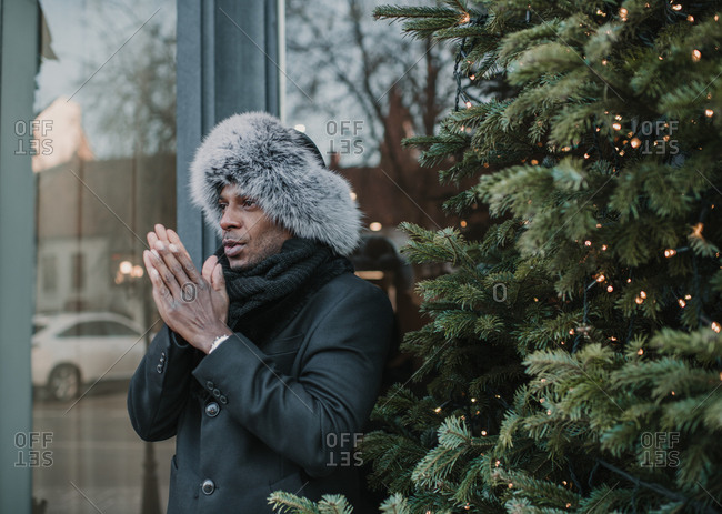 Handsome African American�guy in warm clothes rubbing hands while standing near Christmas tree with fairy lights on city street