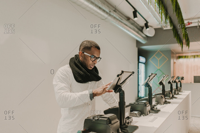 Side view of handsome African American male in�trendy outfit standing near counter in stylish shop and using cash register