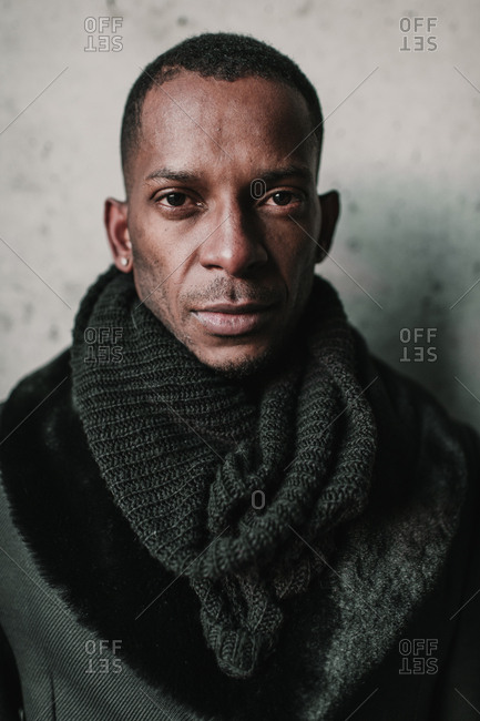 Handsome African American male in stylish warm clothes standing near concrete wall
