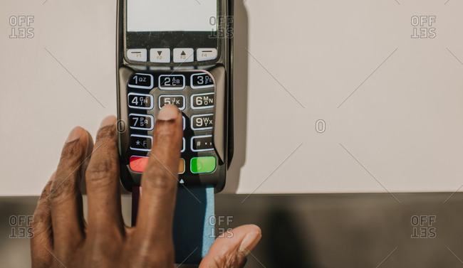 From above shot of hand of African American man pushing buttons on keypad of modern payment terminal