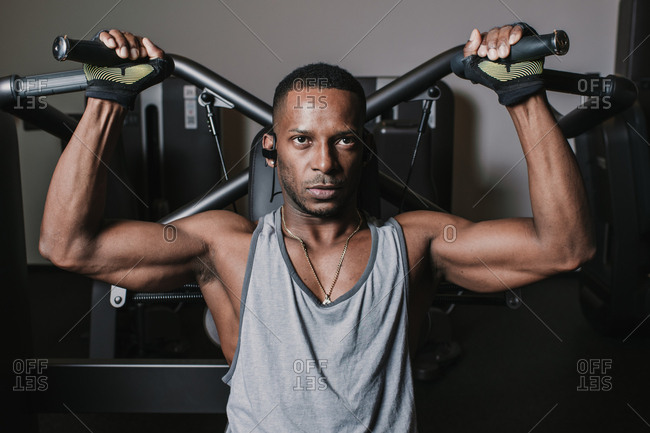 Serious African American guy listening to music and performing exercise on modern machine during workout in gym