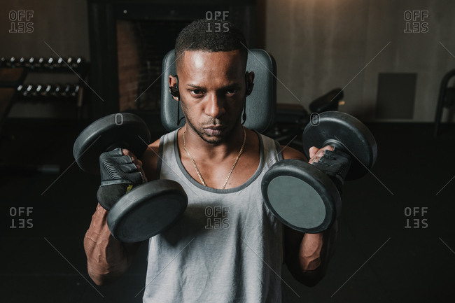 Young African American man lifting two heavy dumbbells and listening to music during training in modern gym
